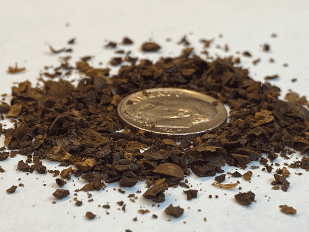 Coarse grind coffee, with a dime for size comparison