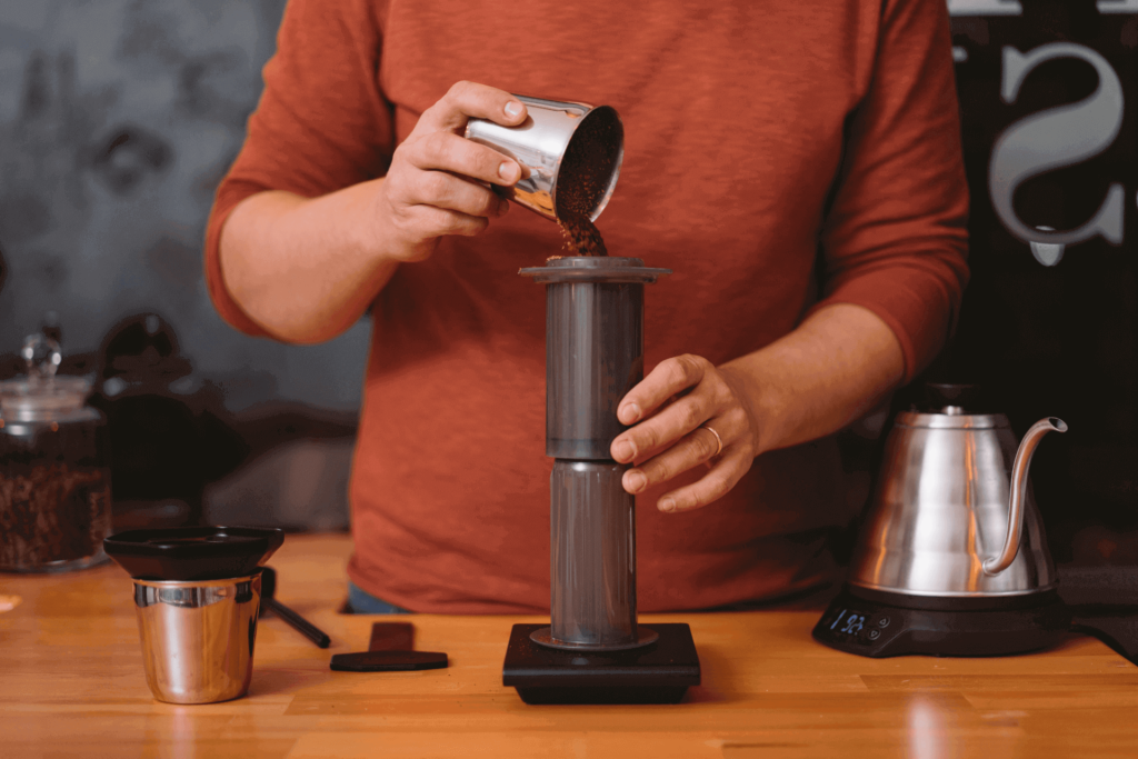 Pouring coffee grounds into an inverted AeroPress coffee maker