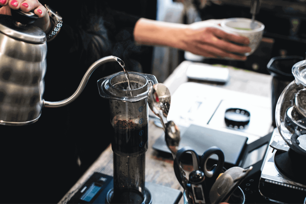 Pouring water into an inverted AeroPress coffee maker from a gooseneck kettle