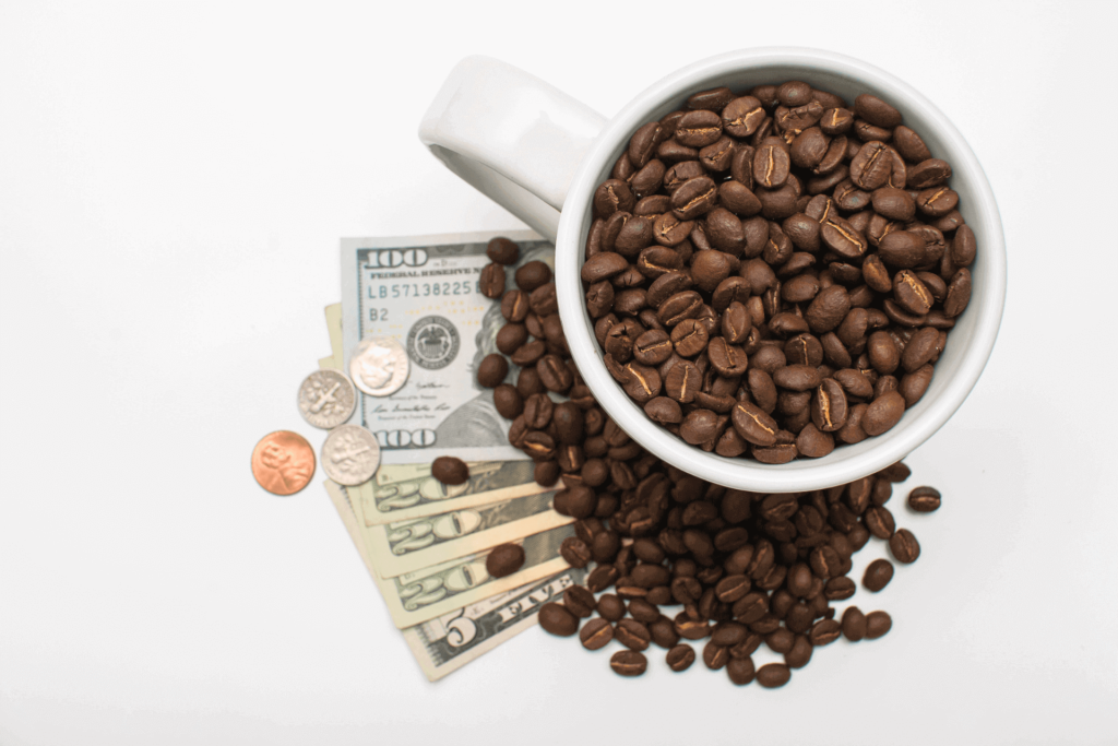A cup of coffee beans on top of some dollar bills, illustrating what a cup of coffee costs