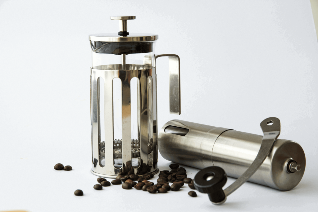 A french press coffee maker and coffee grinder