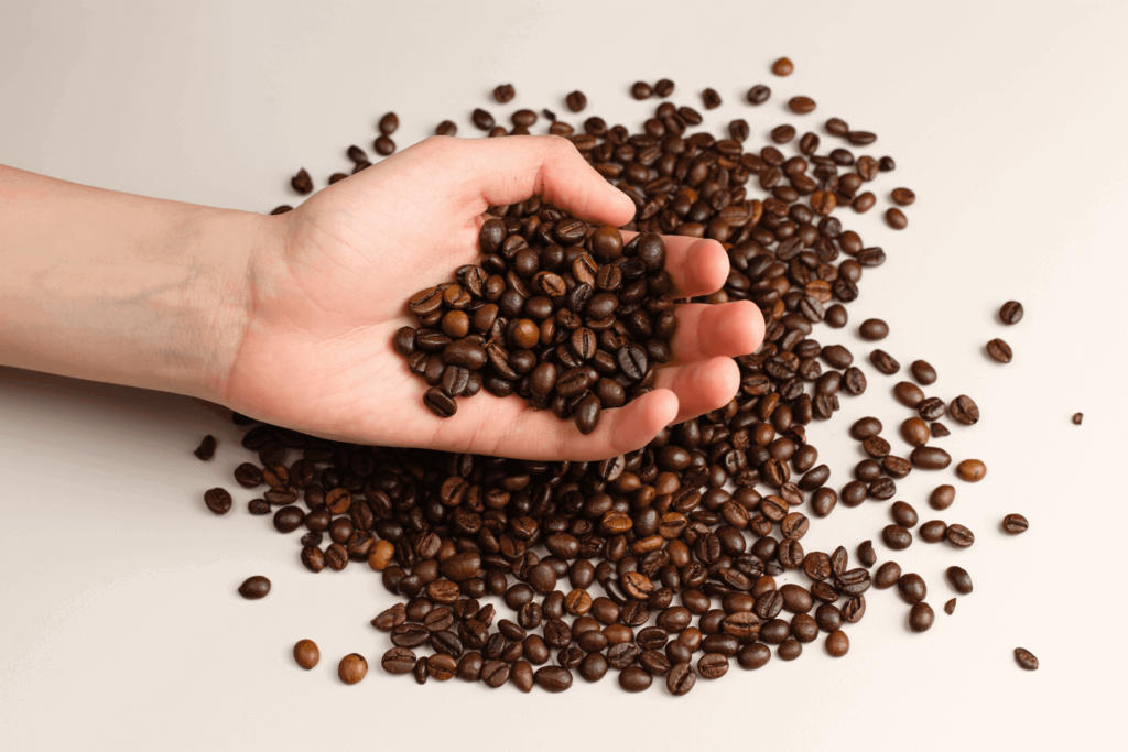 A hand holding coffee beans, like the beans you might use for French press cold brew coffee