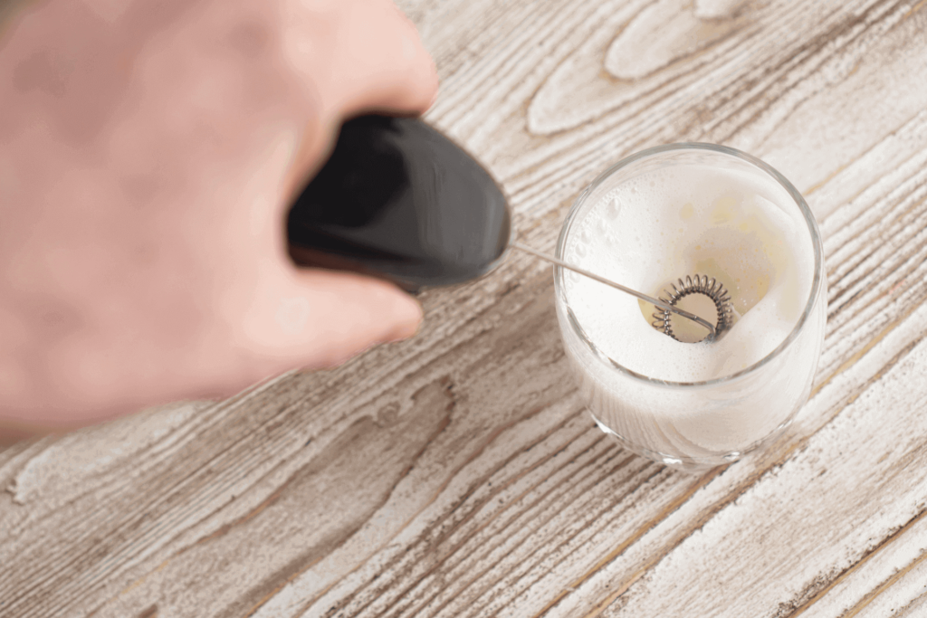 Using a handheld milk frother to prepare steamed milk for a latte